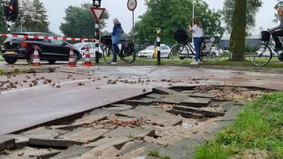 Wethouder Nijhuisstraat in Enschede onder water door lekkage, wegdek en stoep komen omhoog